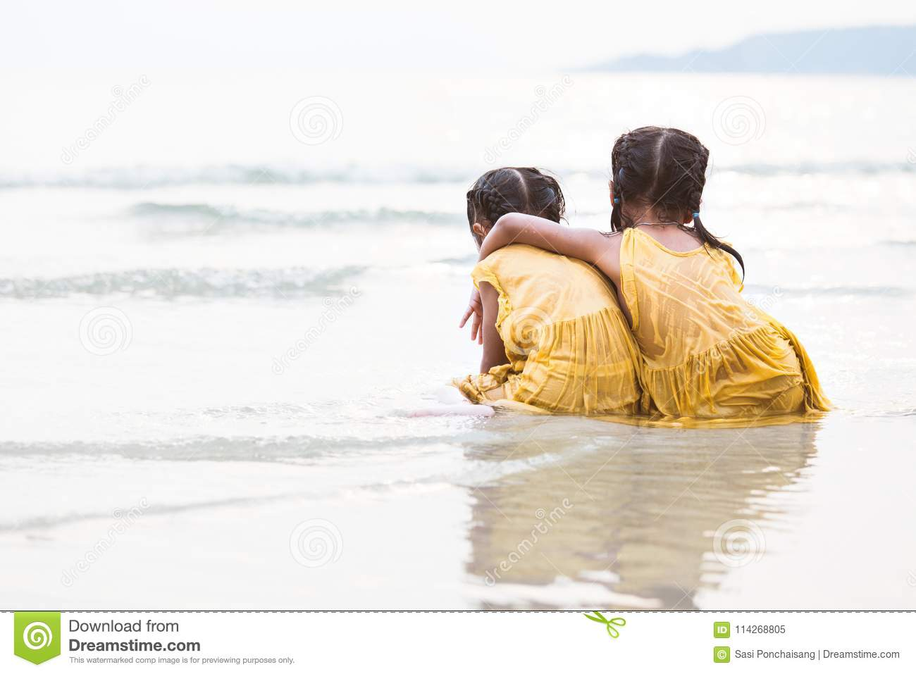 Back view of two cute asian little child girls hugging on beach