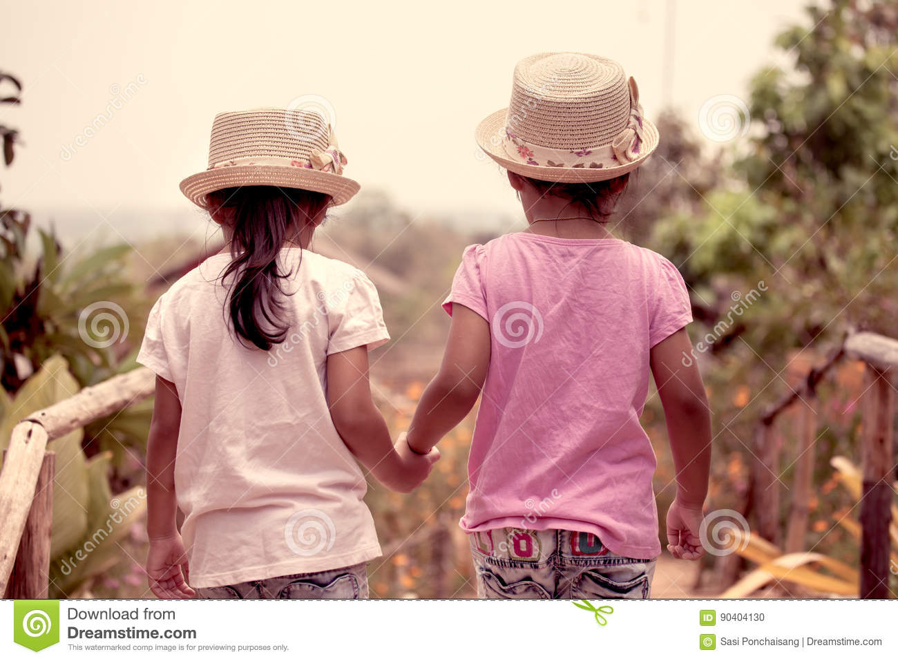 Back view of two little girls holding hand and walking together