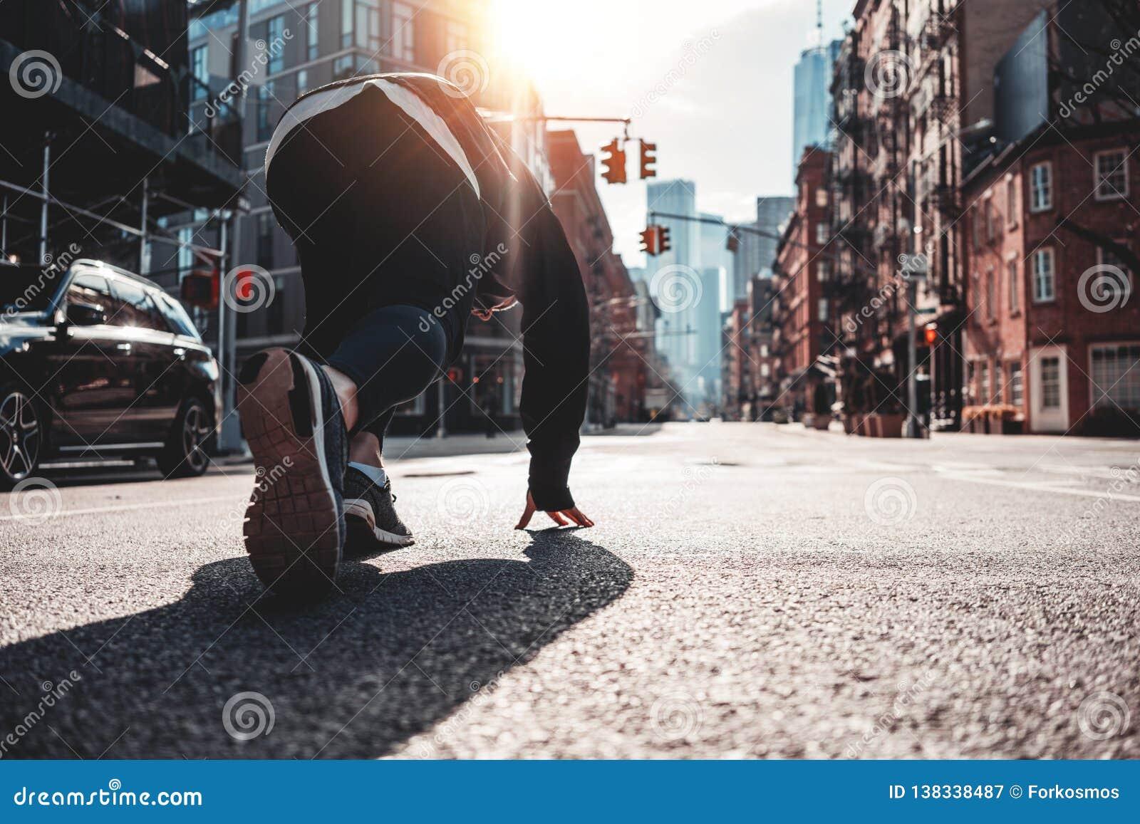 Back view on urban runner in start pose on city street