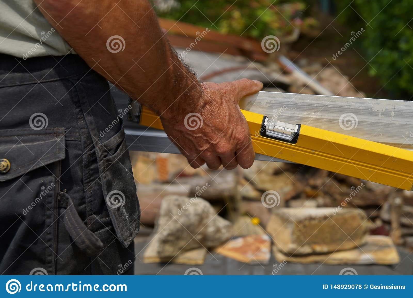 Back view of worker holding a Spirit Level and a straightedge in hand.