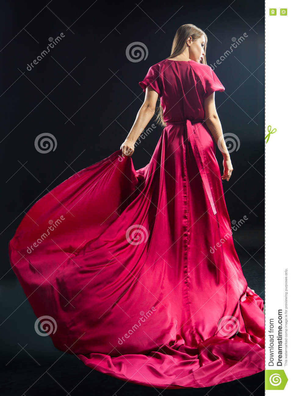 Back view of young blonde woman in bright pink dress