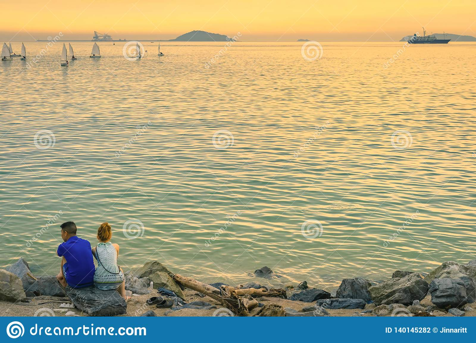 Back view of young couple sitting together on stone in front of ocean enjoying sunset