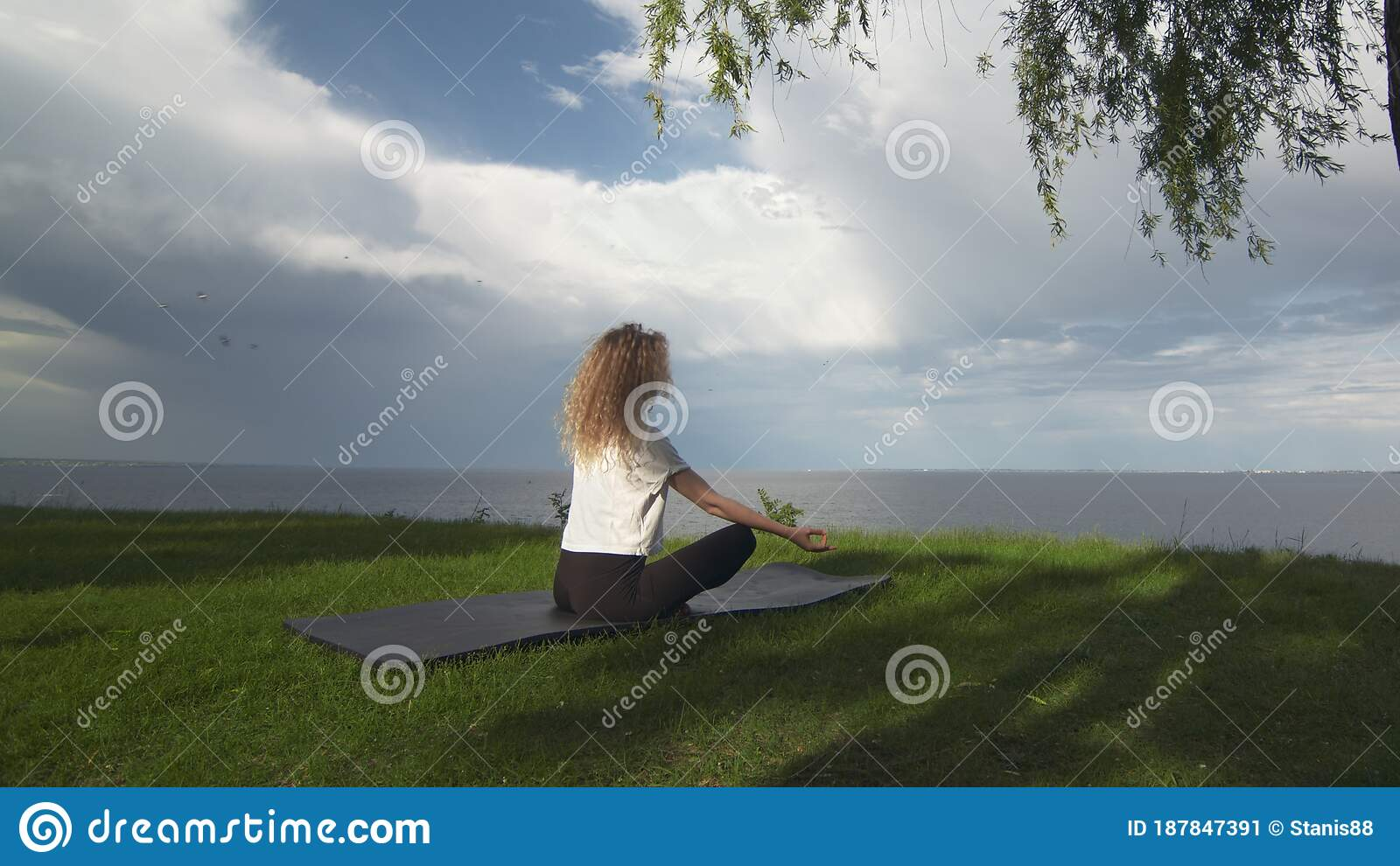Back View Of Young Fit Woman Practice Yoga On Coast Near ...