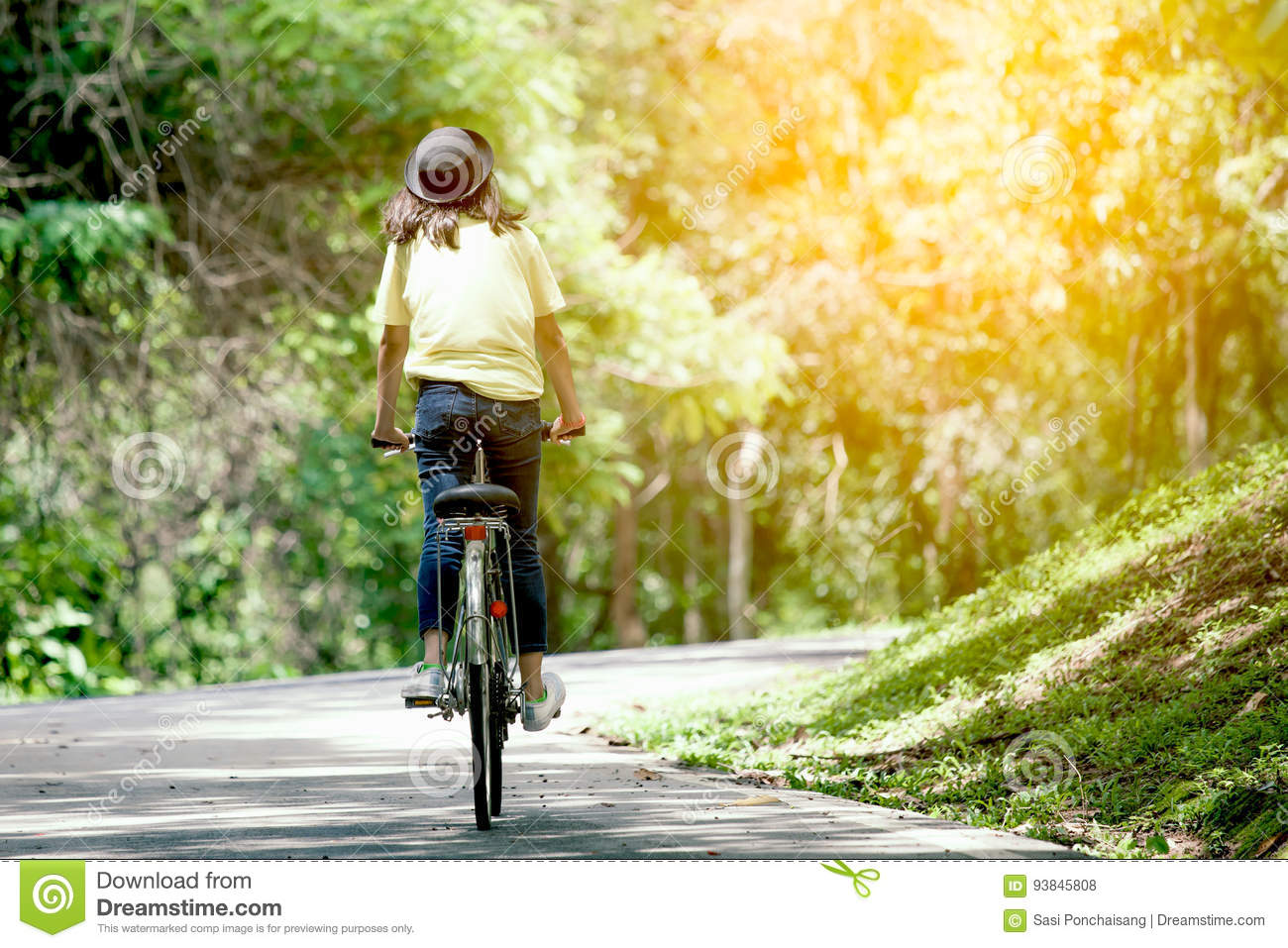 Back view of young girl riding bicycle in the garden