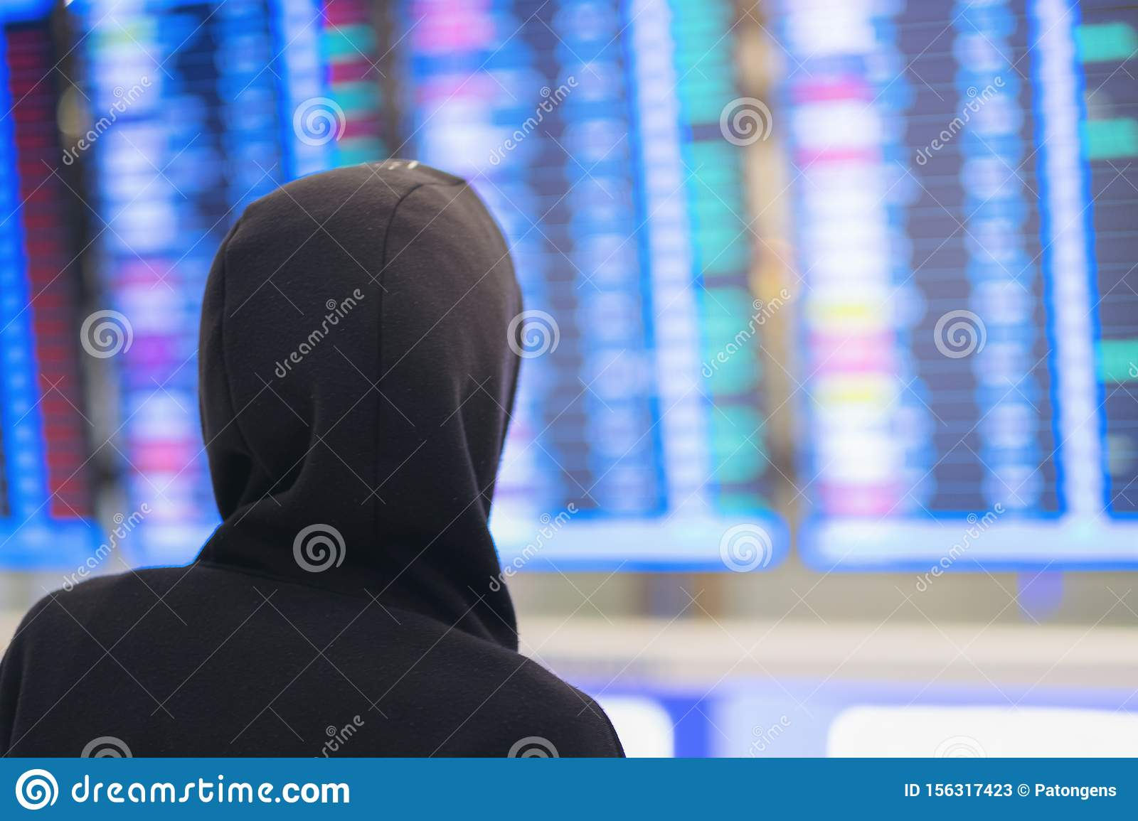 Back view of young man in airport near flight timetable, hacker background of departure board at airport