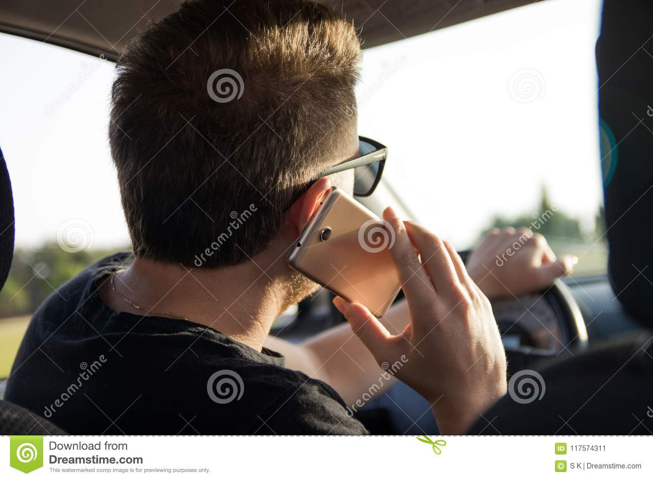 Back view of young man driving a car and talks on the smart phone