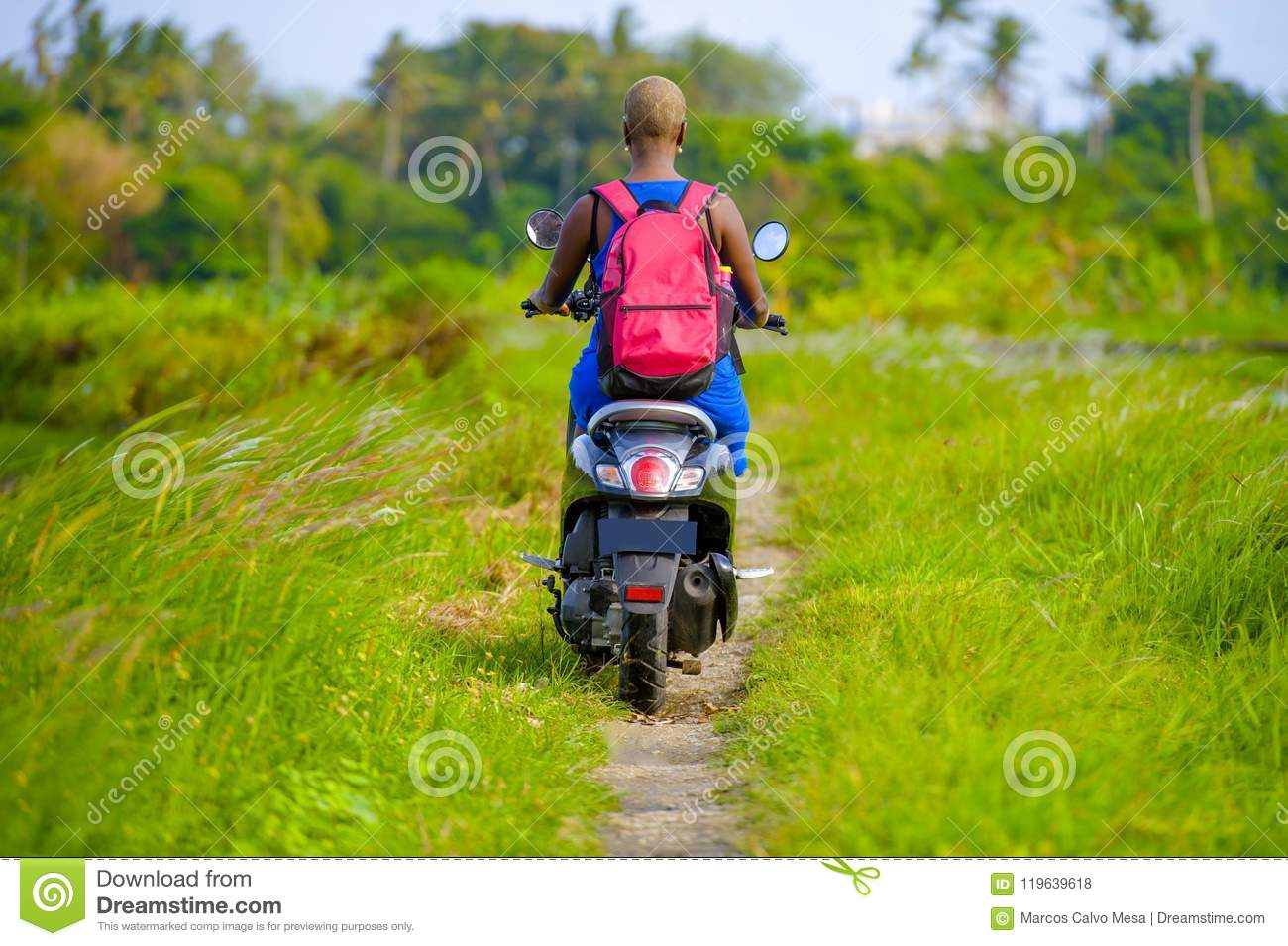 Back view of young tourist afro American black woman riding motorbike happy in beautiful Asia countryside along green rice fields