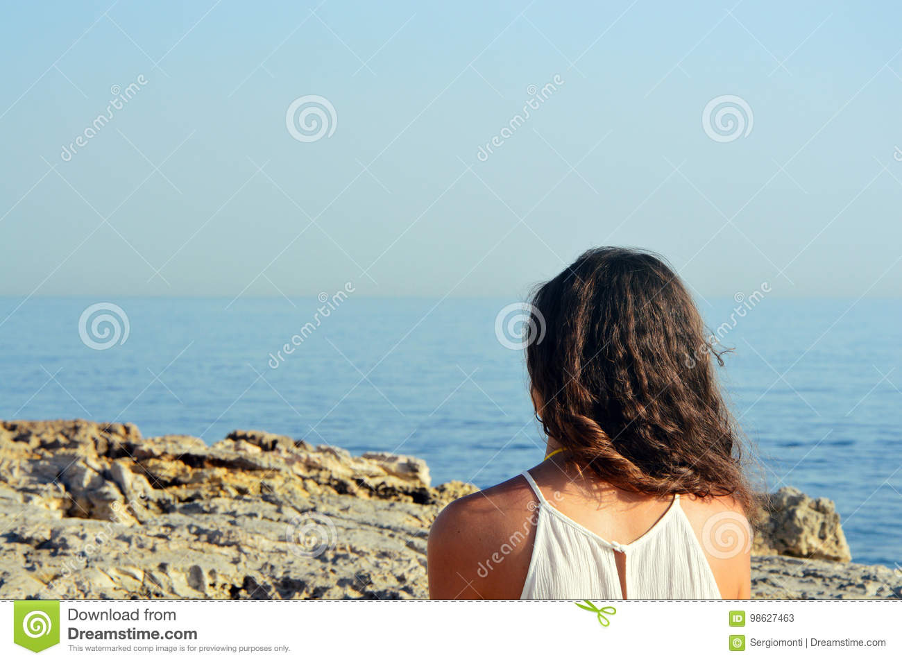 Back view of young woman with curly hair looking at the sea from rocky coast. Traveler on background beach.