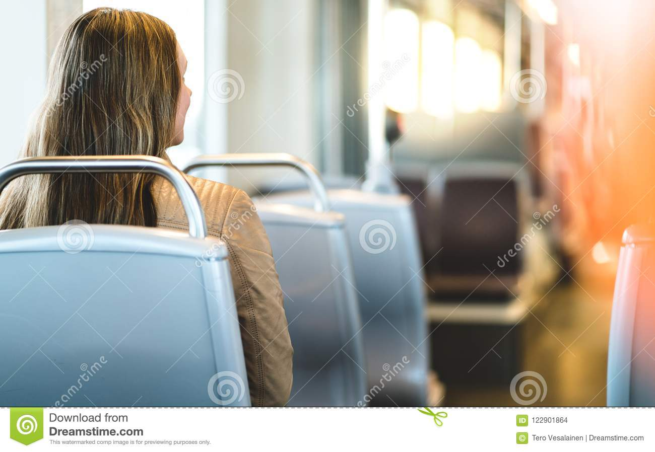 Back view of young woman sitting in public transportation