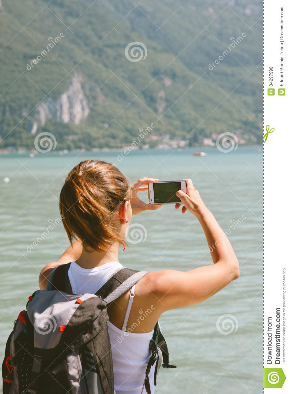 Back view of young woman taking photos with mobile phone.