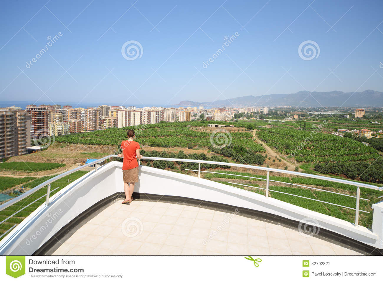 Back of woman standing on balcony of hotel