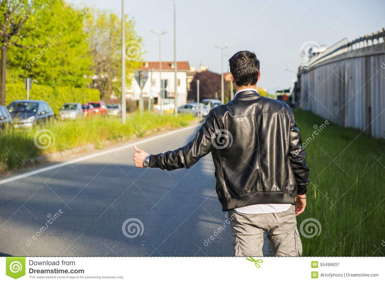 Back of young man, hitchhiker waiting on roadside