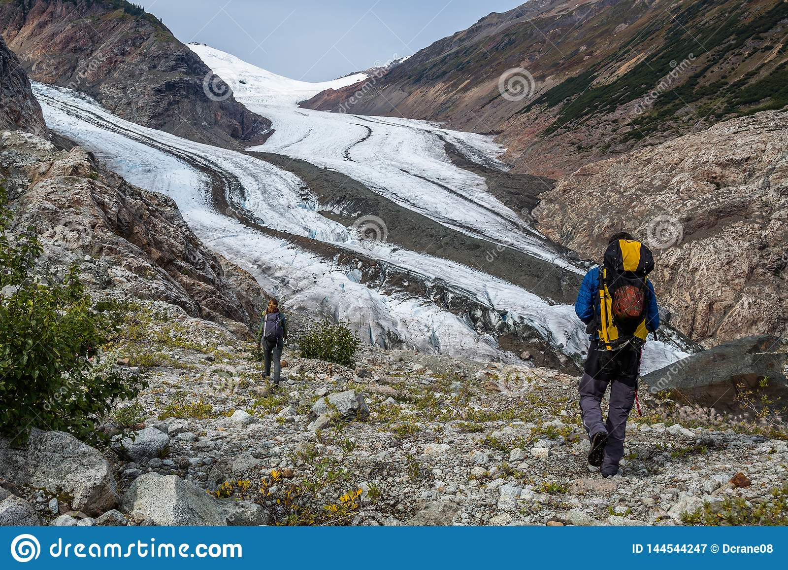 Backcountry die dichtbij grote gletsjer in Canada wandelen Man en vrouw die een rand boven een gletsjer in de Grenswaaier lopen v