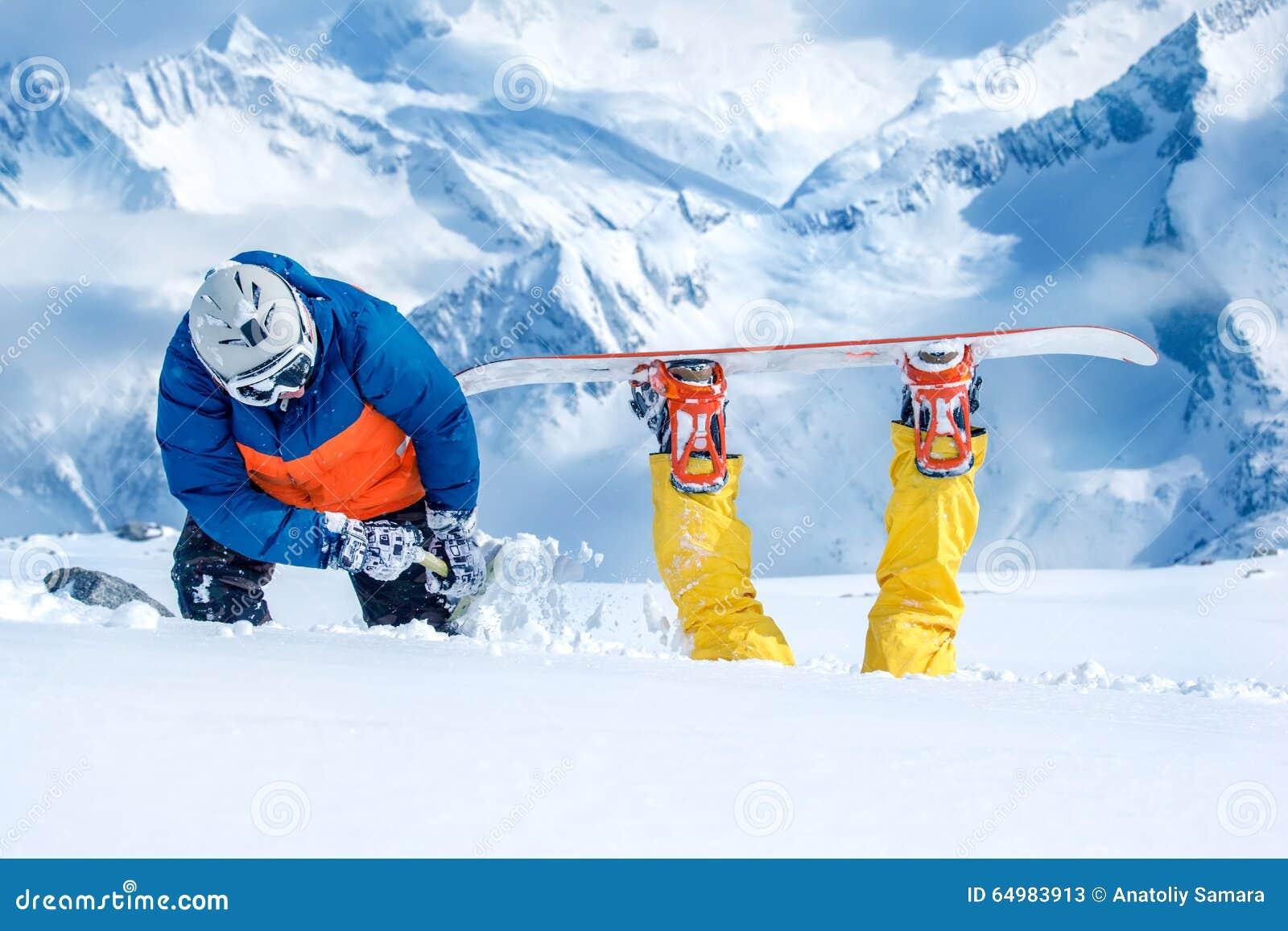Backcountry snowboarder som ut gräver hans vän