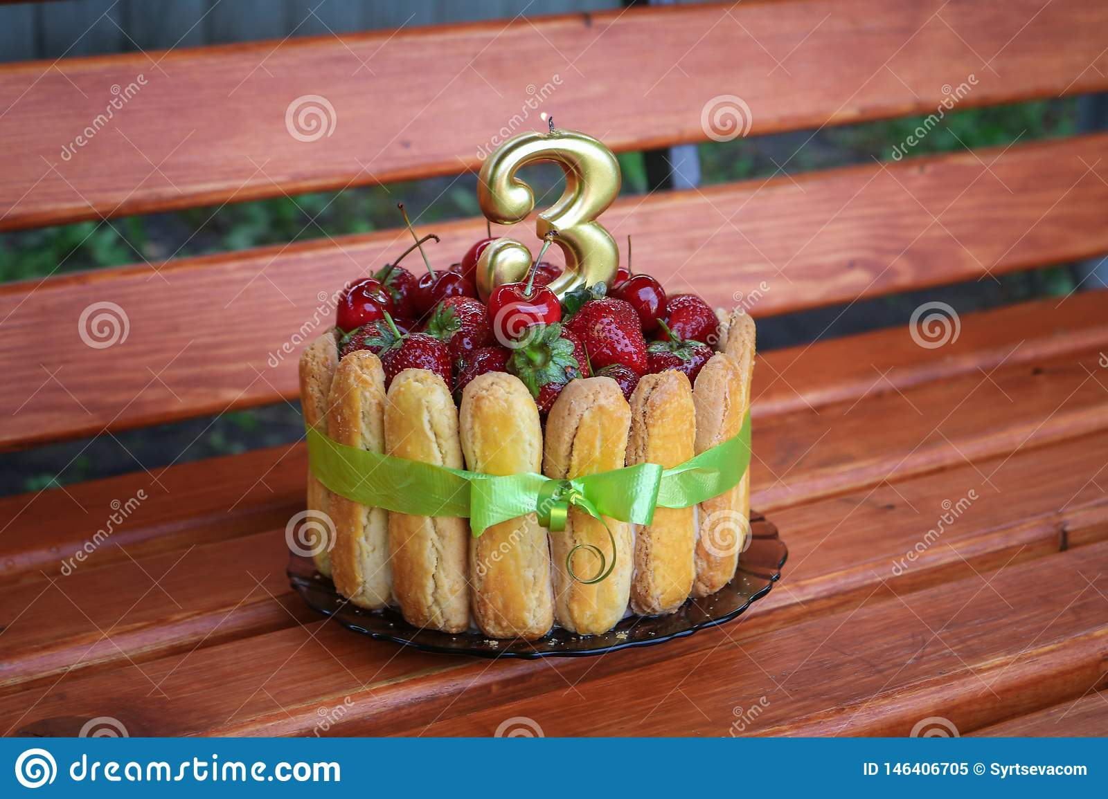 Birthday cake with strawberries and cherries on a wooden background