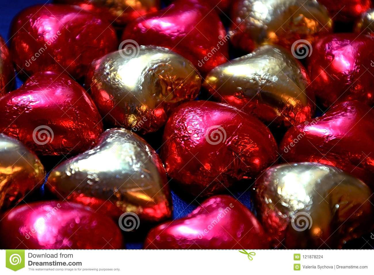 Background of chocolate candies in the form of hearts close-up. Red and gold packaging made of shiny foil.