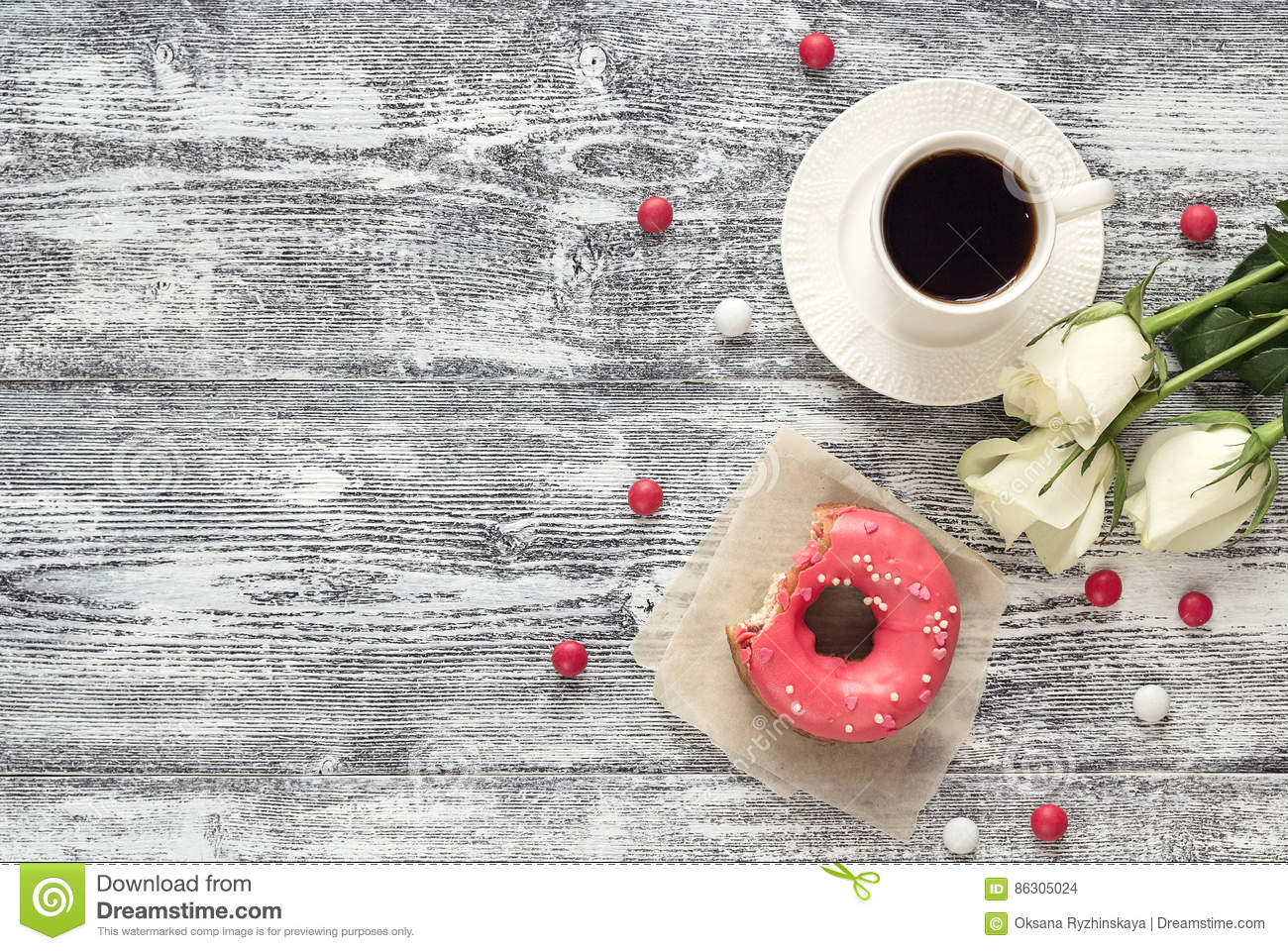 Background with cup of coffee, donut and white roses on a gray