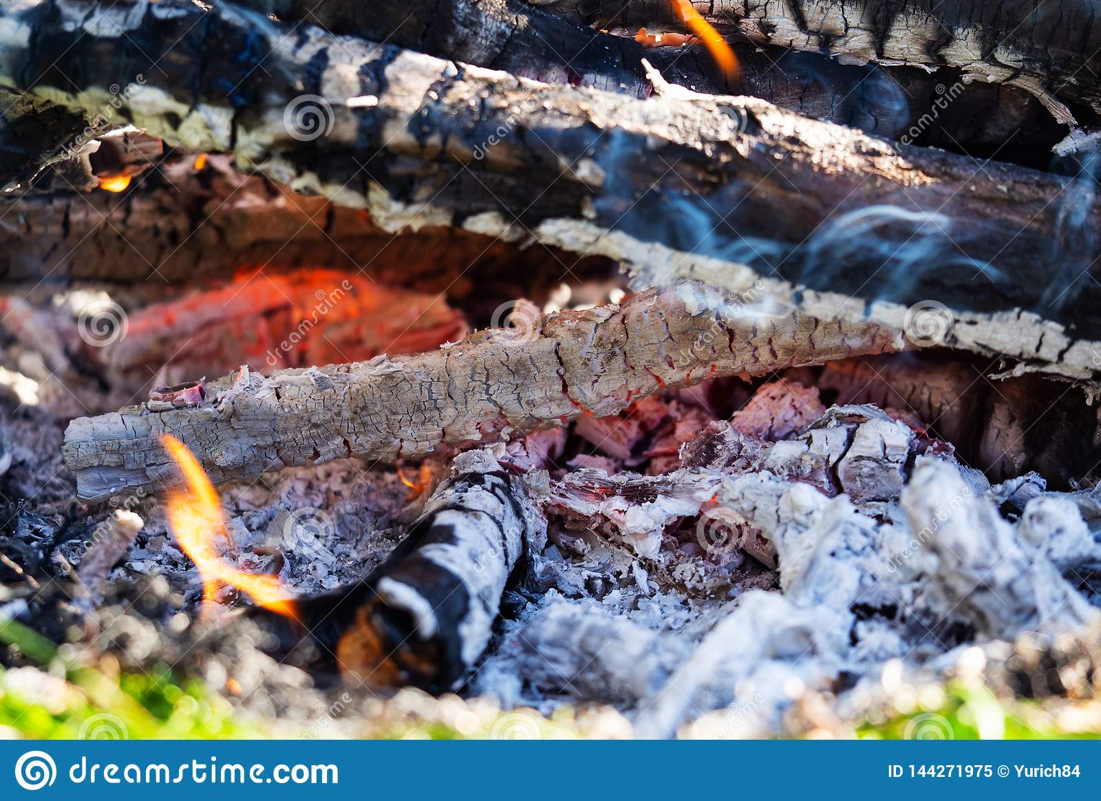Background of fireplace with gloving embers. Close up view on smouldering fire. Embers burning with red flame. Texture of ash and