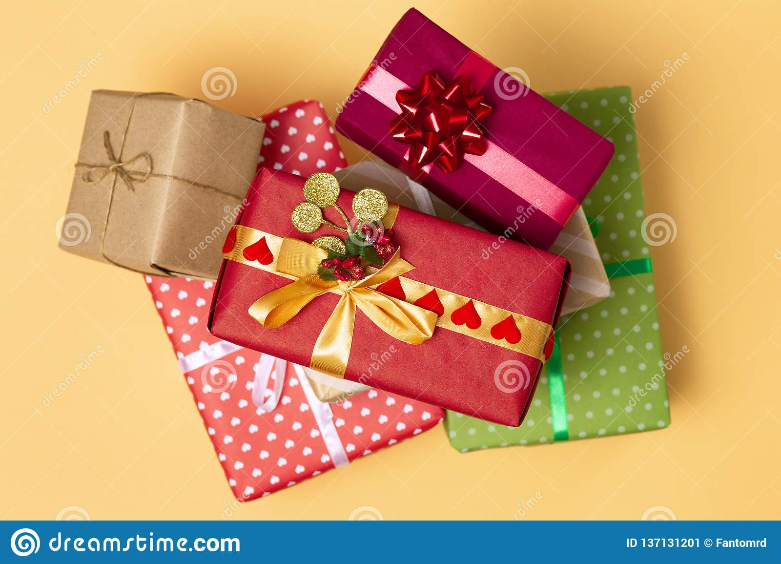 Background Of Gifts Boxes Wrapped In Decorative Paper On A Colored