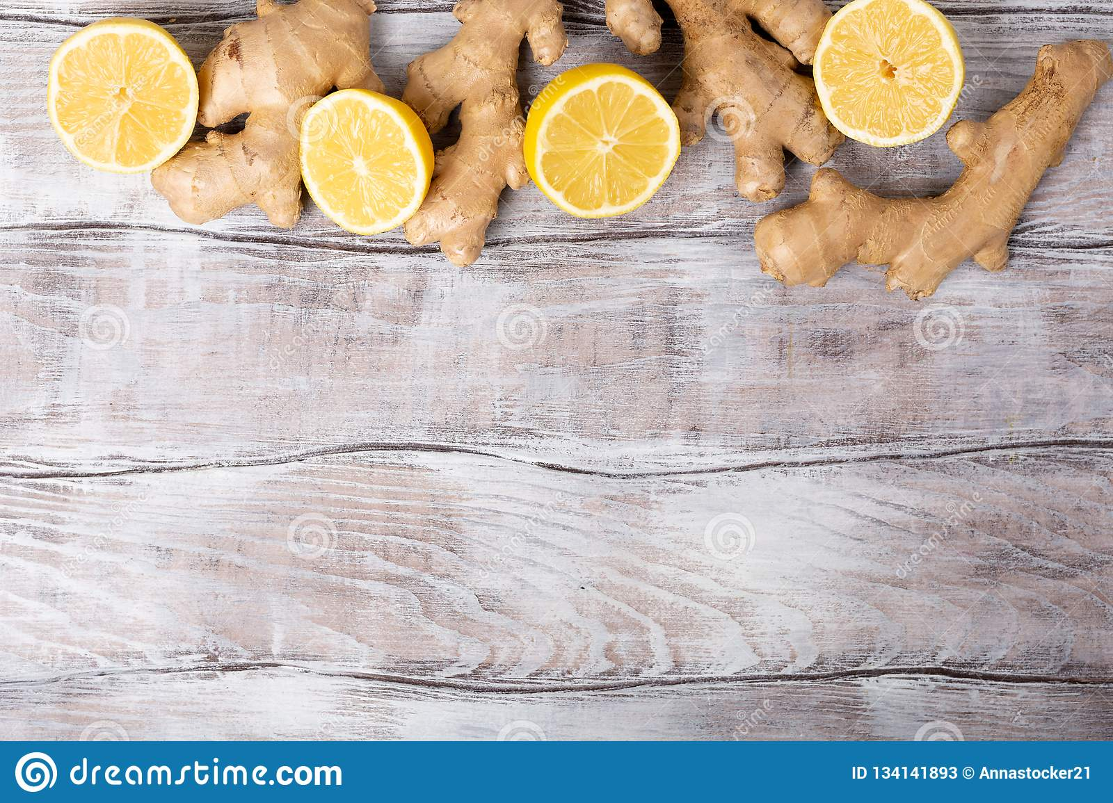 Background. Healthy food. Ingredients for detox lemonade, lemon and ginger on white wooden background, top view, copy