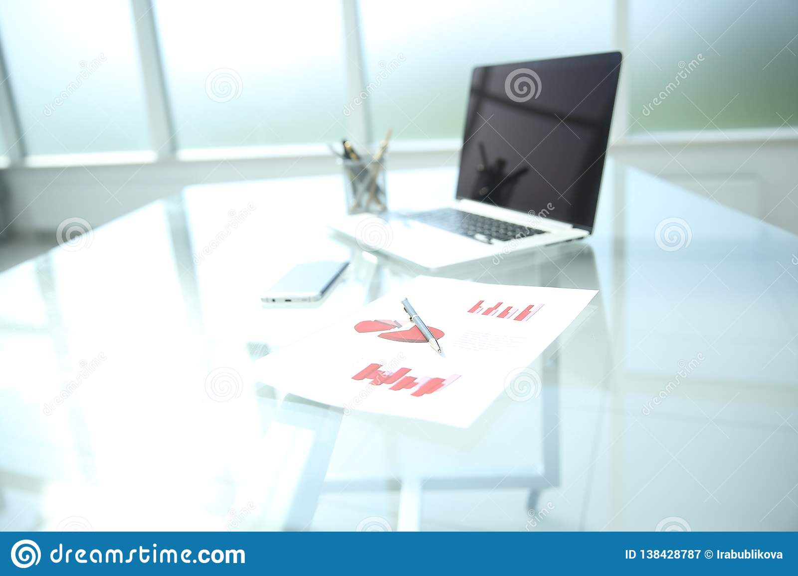 Background image is a financial chart and a pen on the table