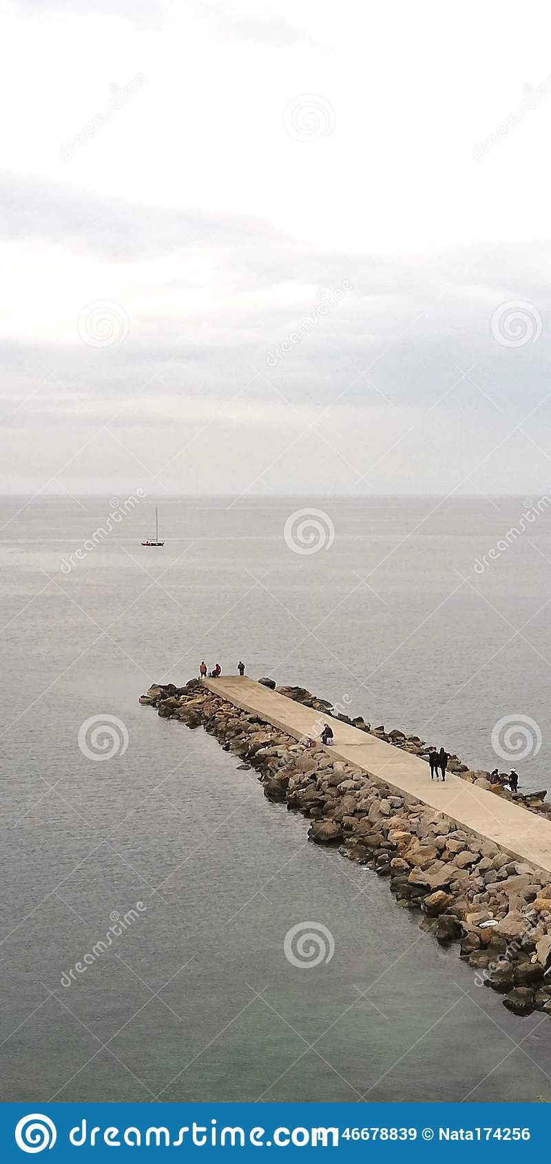 Background. Sea evening landscape. On the stone mall are visible silhouettes of people.