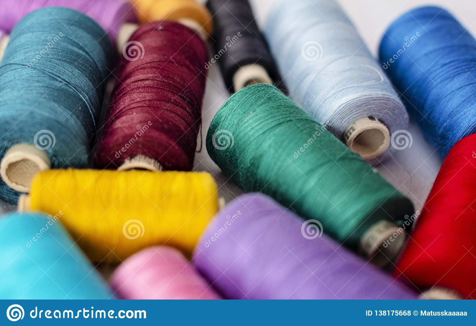 Background shot of bright thread spools on white fabric - image