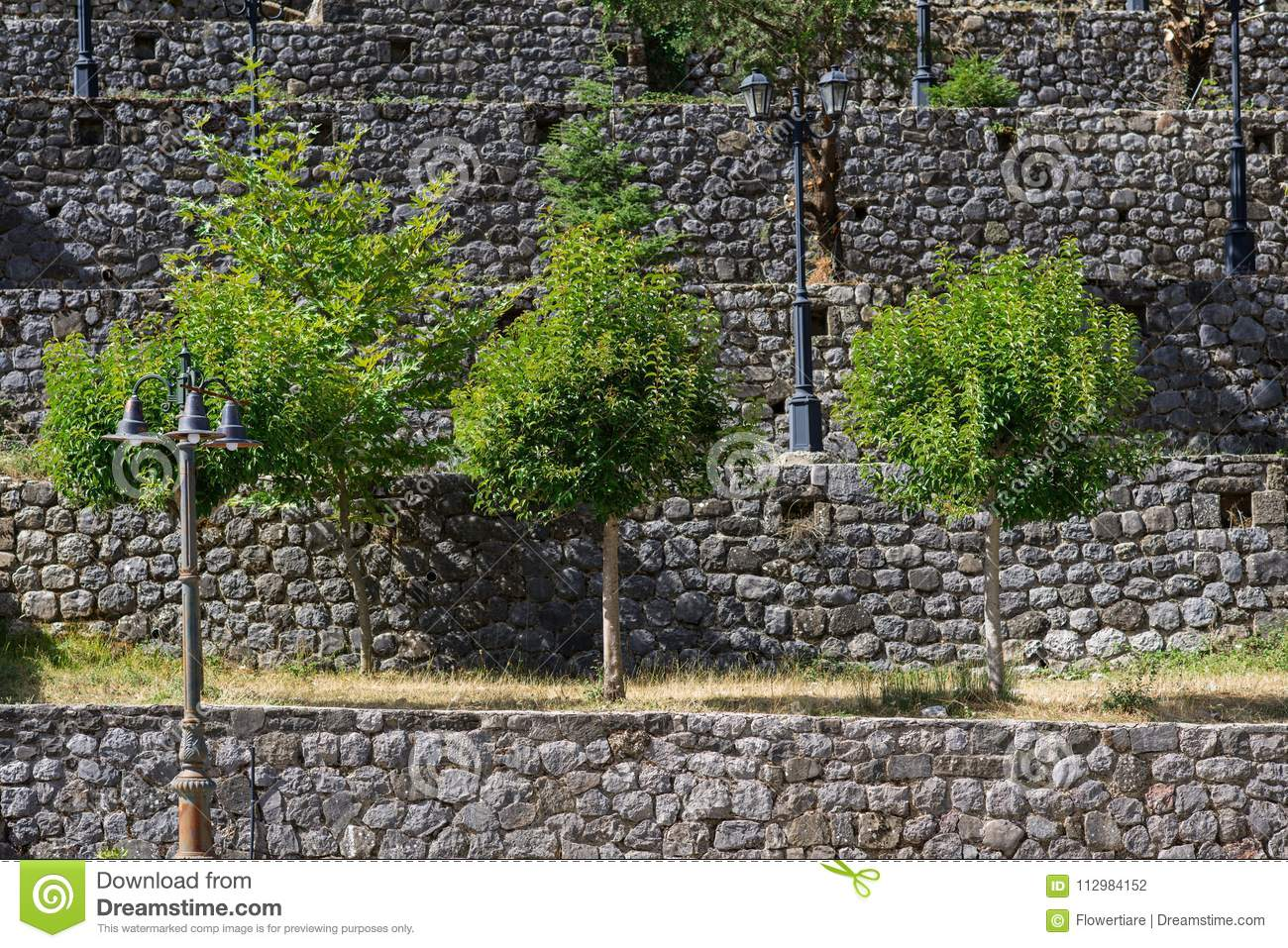 Background of a brick wall with trees and lanterns