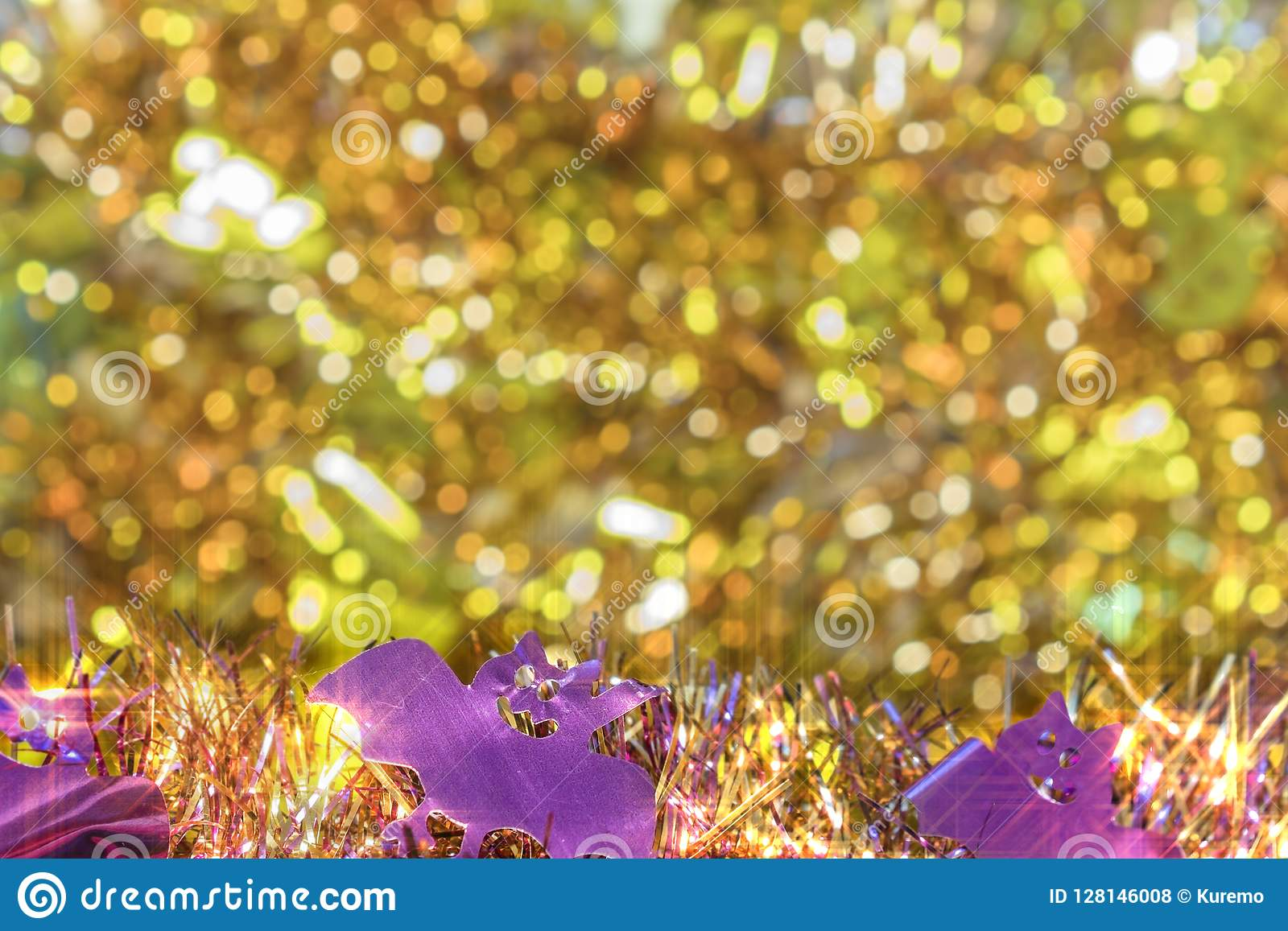 Background texture full of small golden bokeh with garlands decorated of purple smiling bats faces in foreground to celebrate