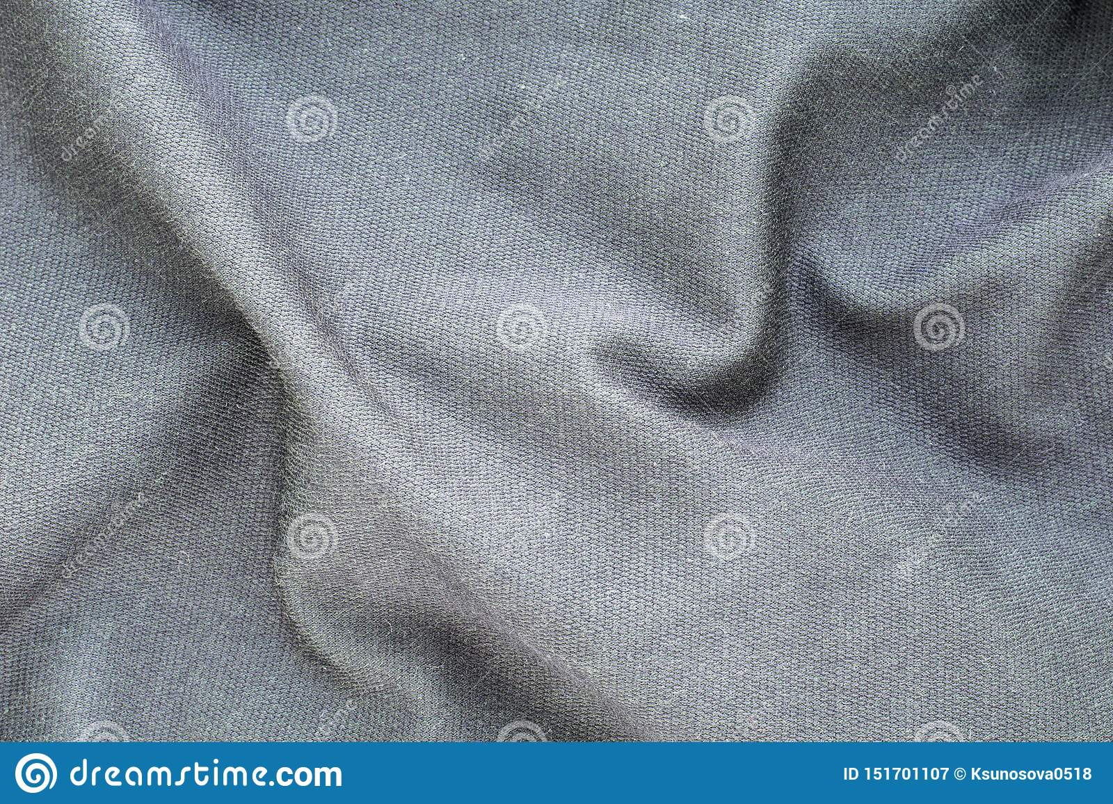 The background texture is a gray soft wavy fabric, top view, close-up.
