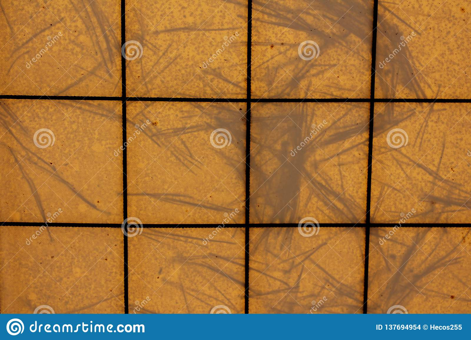 Background texture pattern made of dark metal wires and yellow tarpaulin with pine needles on top all shaped like yellow tiles