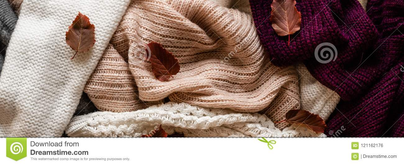 0f789ef254 Background with warm sweaters. Pile of knitted clothes with autumn leaves