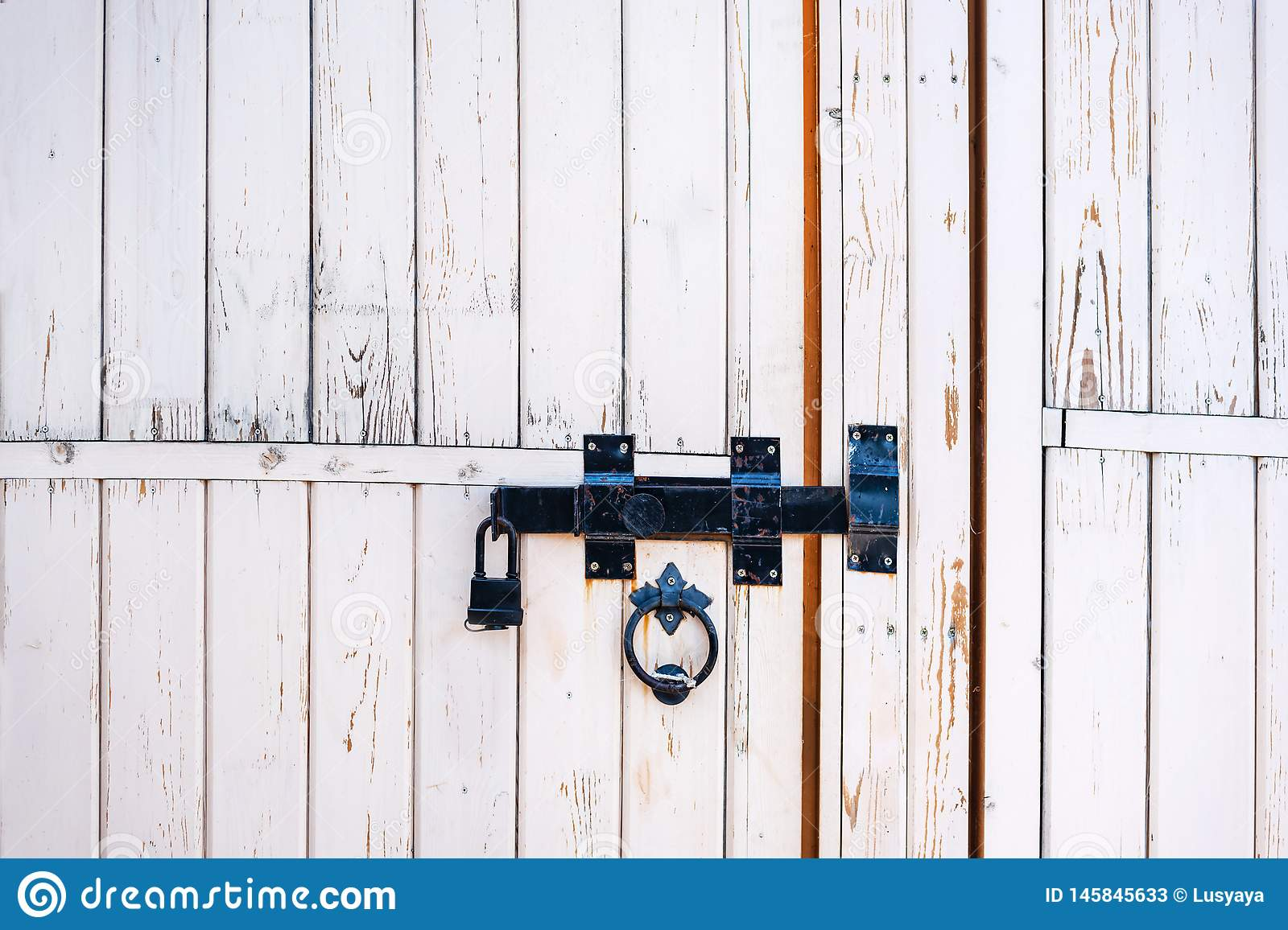 Backgrounds and textures: old white wooden door, closed with traditional forged metal lock