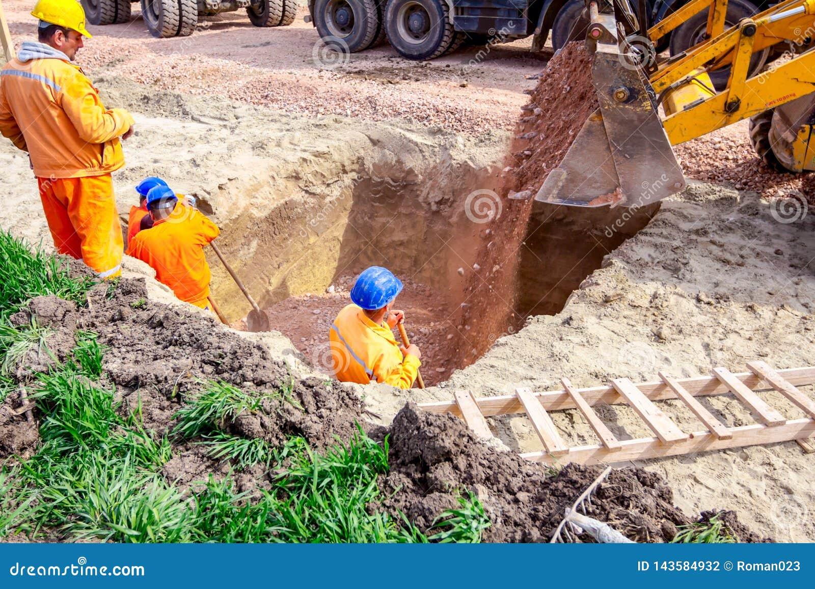 Backhoe χύνει το αμμοχάλικο στην τάφρο στο εργοτάξιο οικοδομής