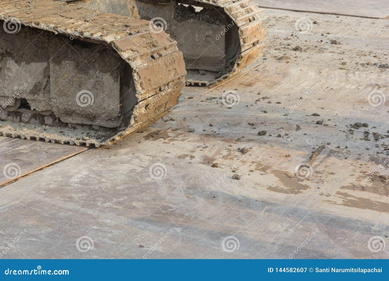 Грязные колесо и грязь backhoe на колесе