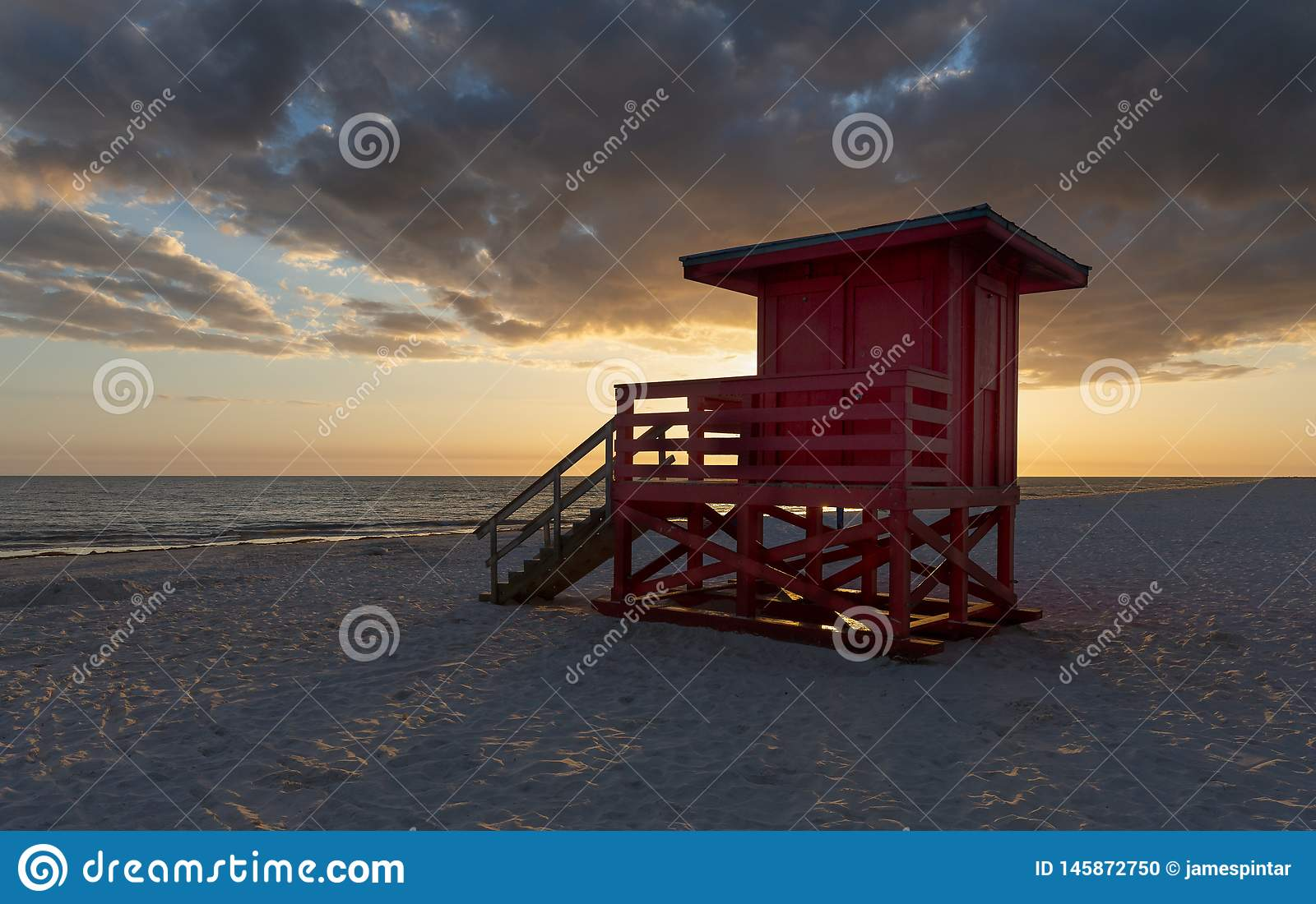 Backlit Lifeguard Tower at Sunset. Red lifeguard tower seen in partial silhouette and set against a cloud filled sky at sunset stock photo