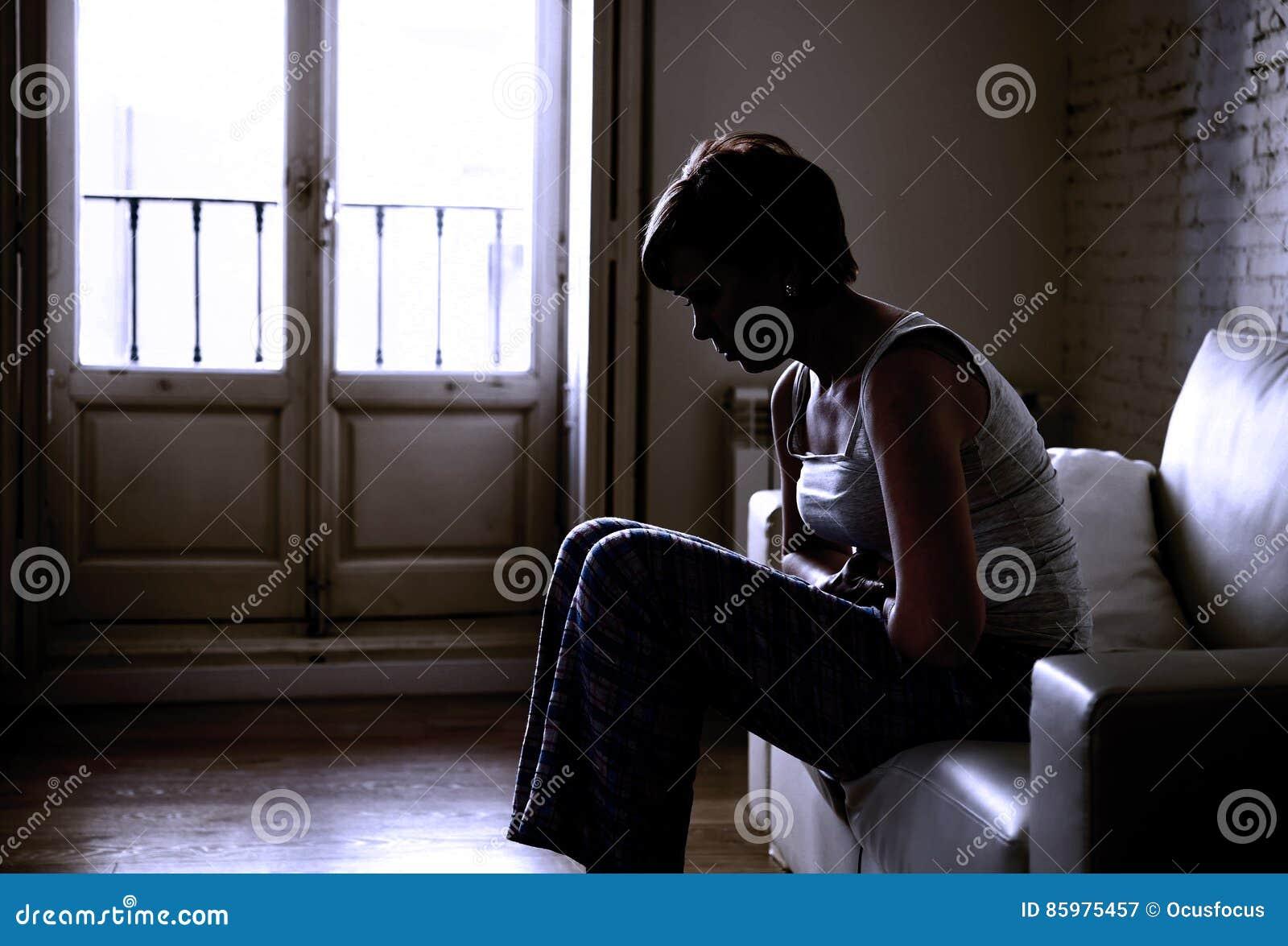 Backlit silhouet van jonge vrouwenholding die buik kwetsen die maag aan klem en periodepijn lijden