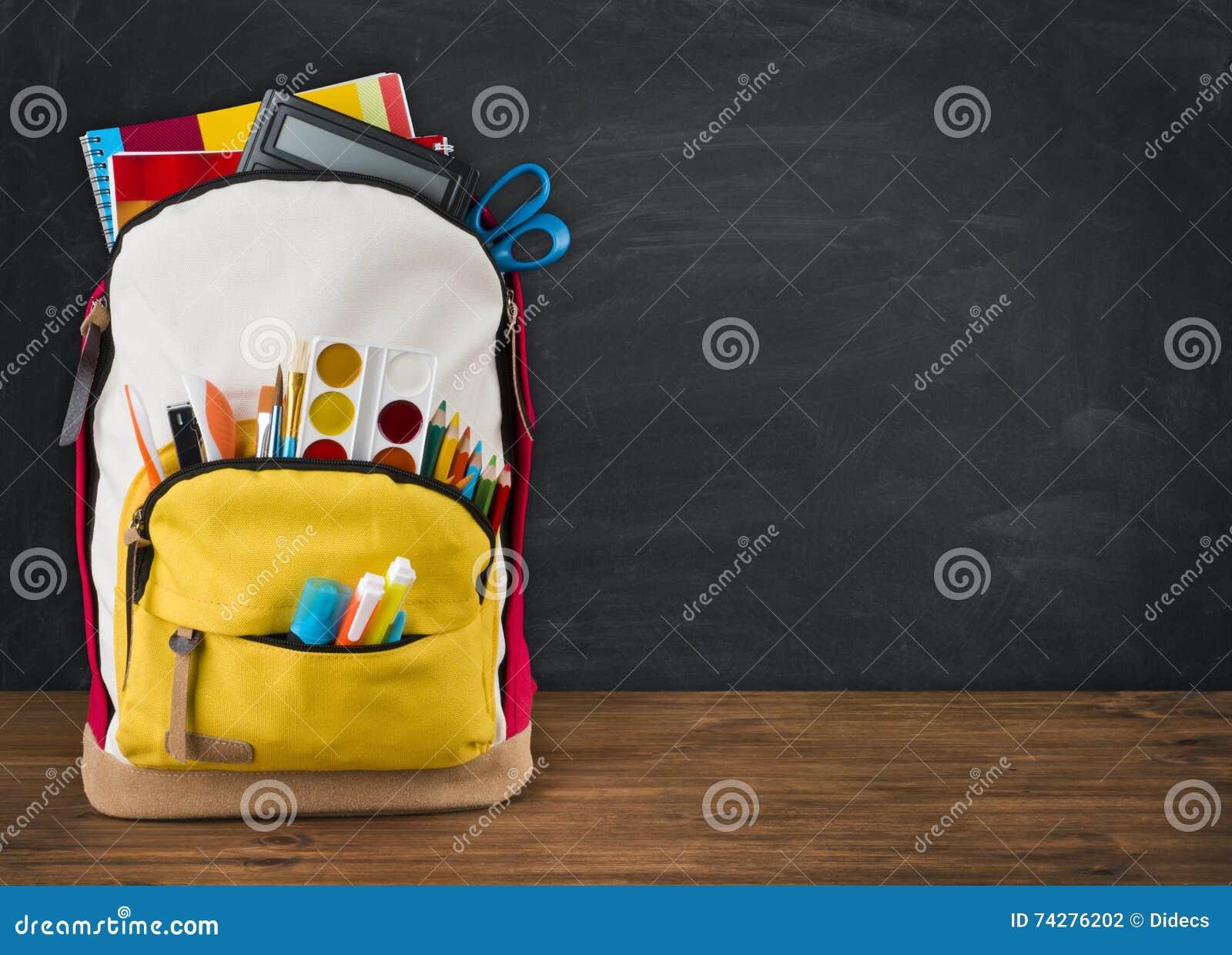 Backpack completamente das fontes de escola sobre o fundo preto da administração da escola