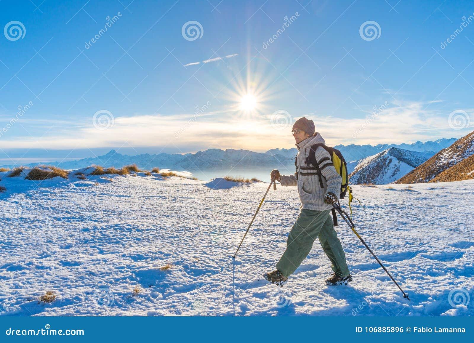 Backpacker женщины trekking на снеге на Альпах Вид сзади, образ жизни зимы, холодное чувство, звезда солнца в backlight, пеших по