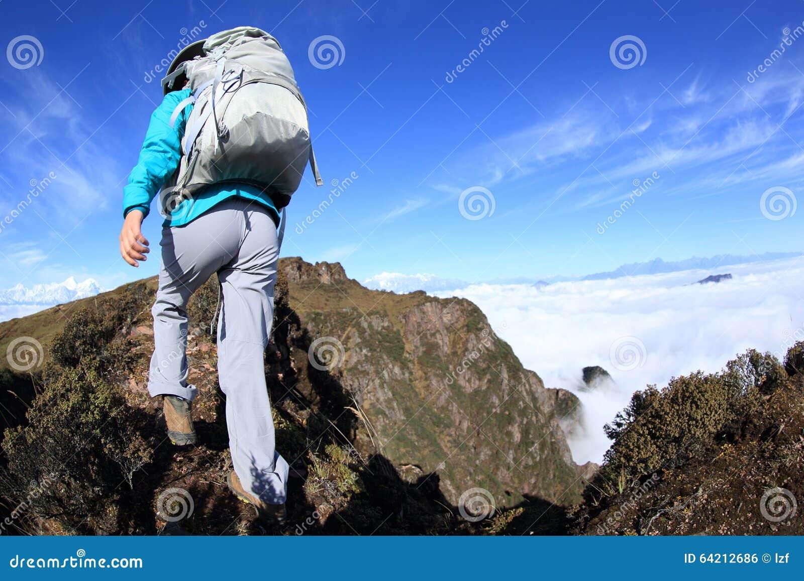 Backpacker de la mujer que camina en el pico de montaña hermoso