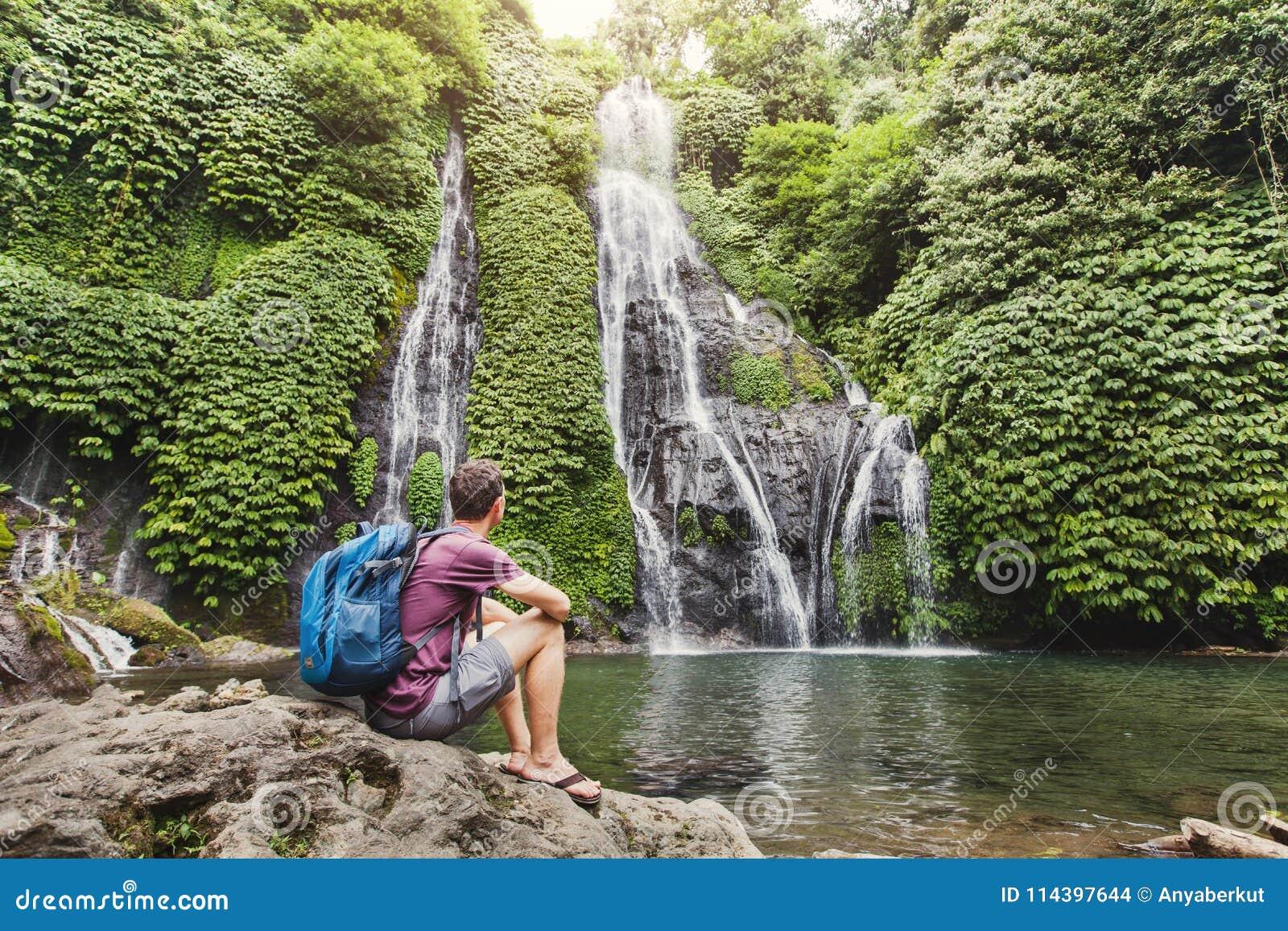 Backpacker die waterval in Bali, toerisme bekijken