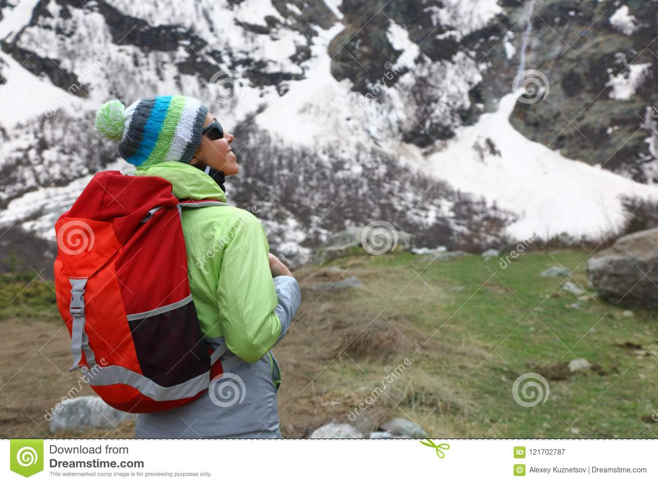 Backpacker girl stands on top of a mountain