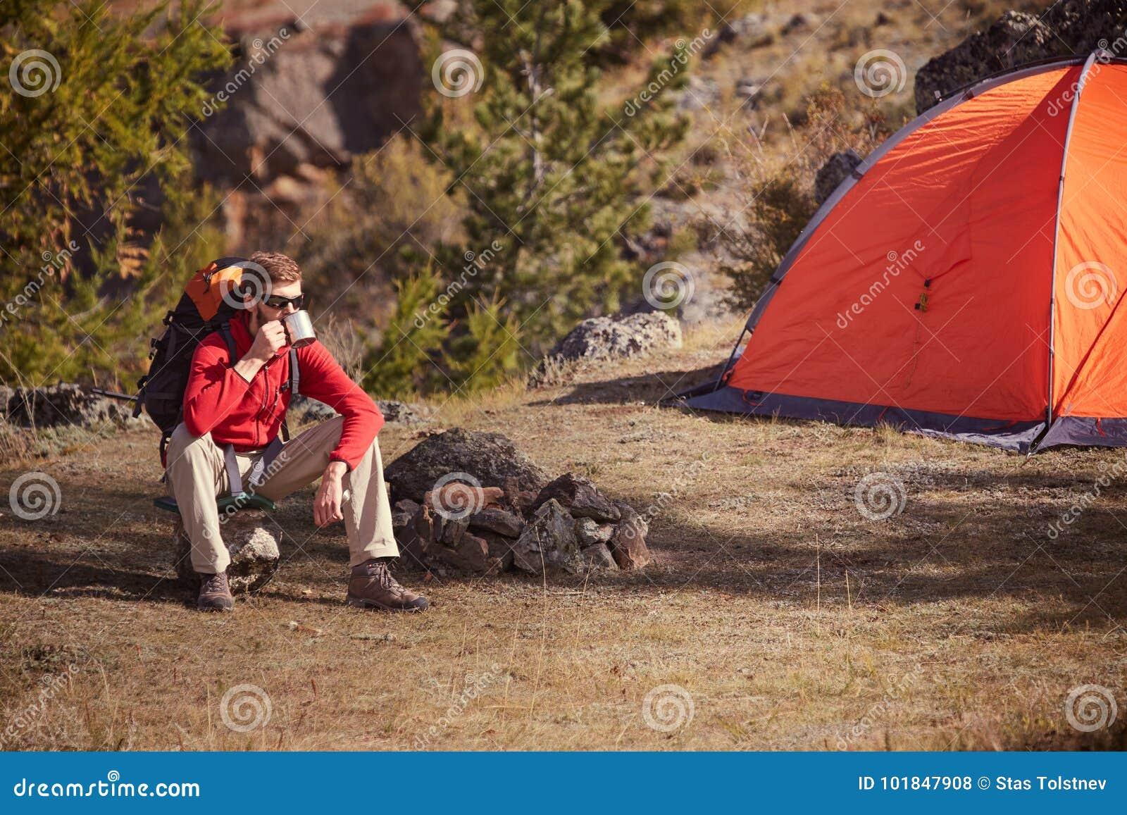 Backpacker Having Rest Near Orange Tent, Drinks Tea From Cup   Stock