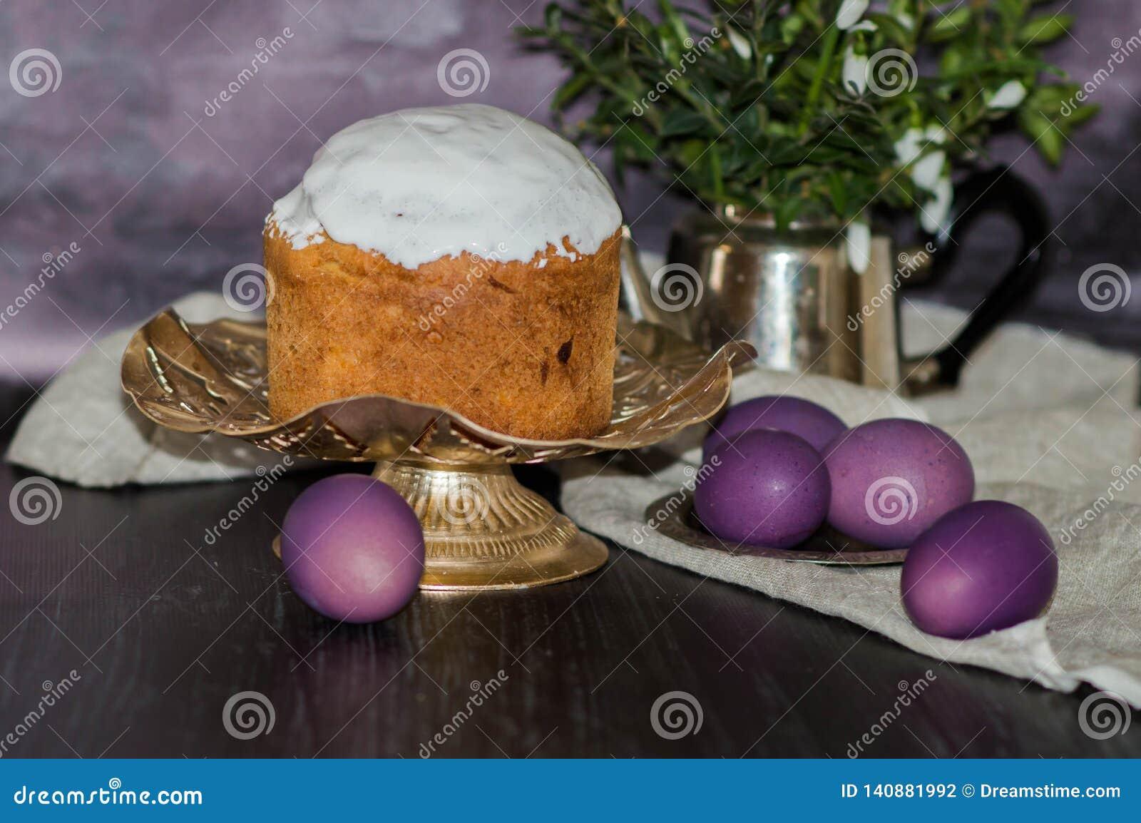 Backte frisch Ostern-Kuchen auf dem Küchentisch, der mit Zuckerglasur bedeckt wurde und Belag mit purpurroten Eiern verziert war