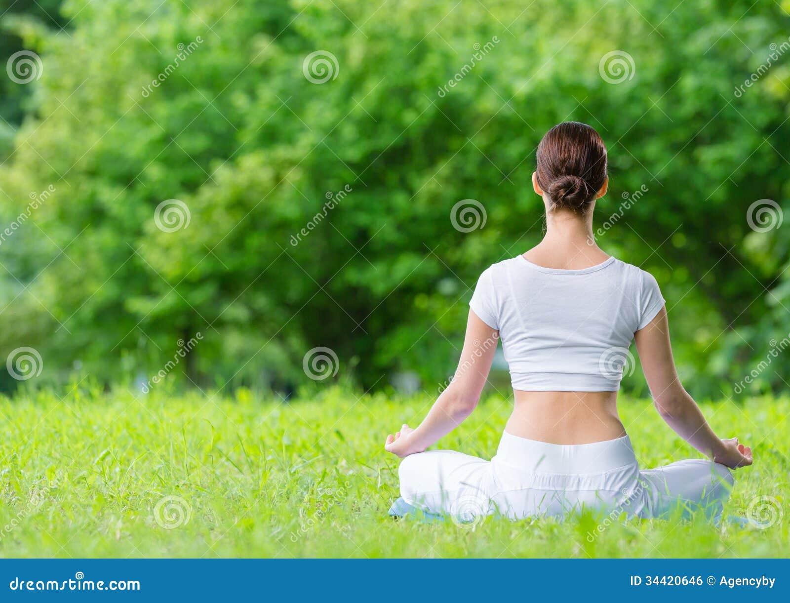 Backview av kvinnan, i att göra en gest för zen för lotusblommaposition