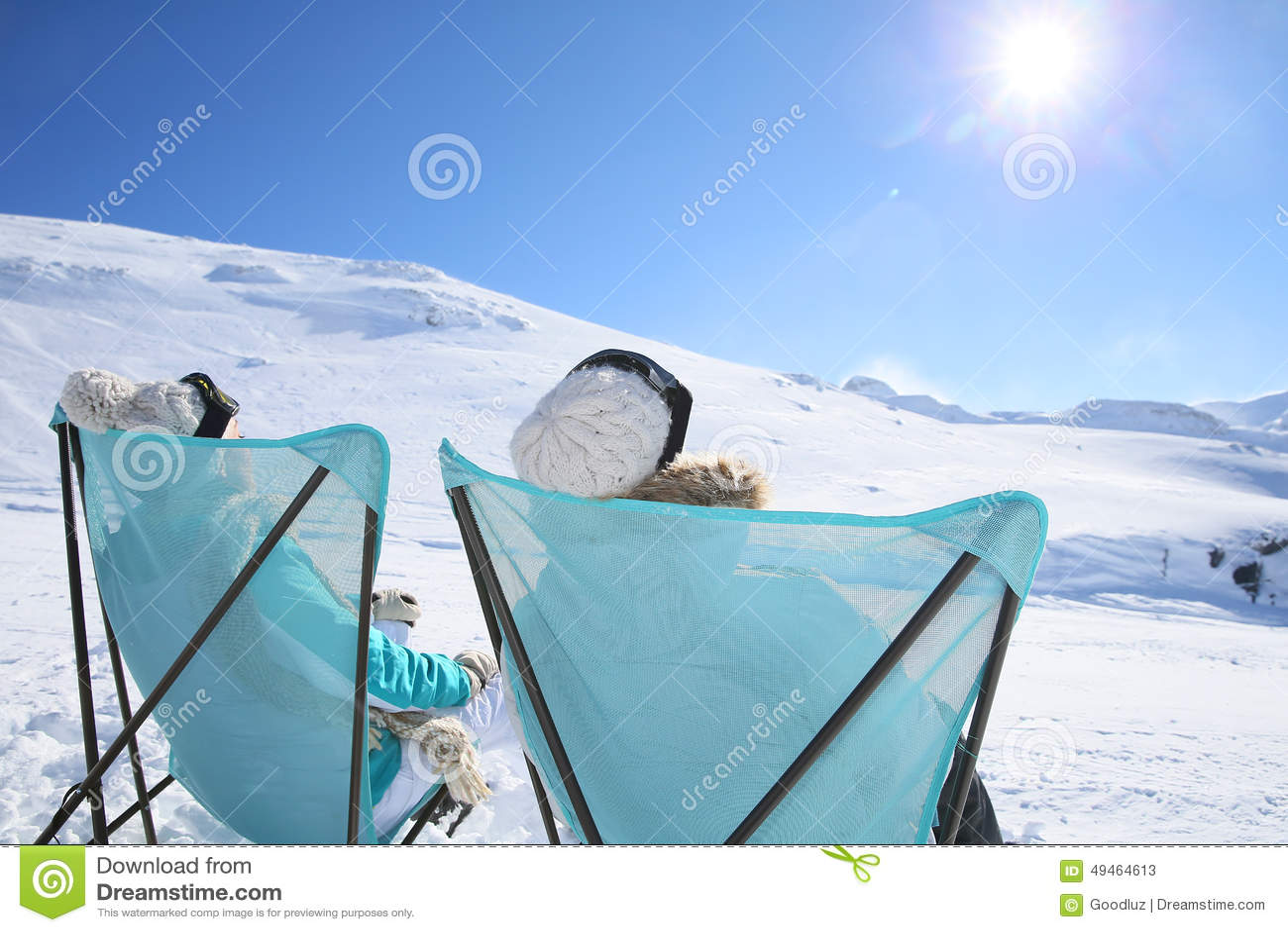 Backview of a couple taking sun on ski slopes