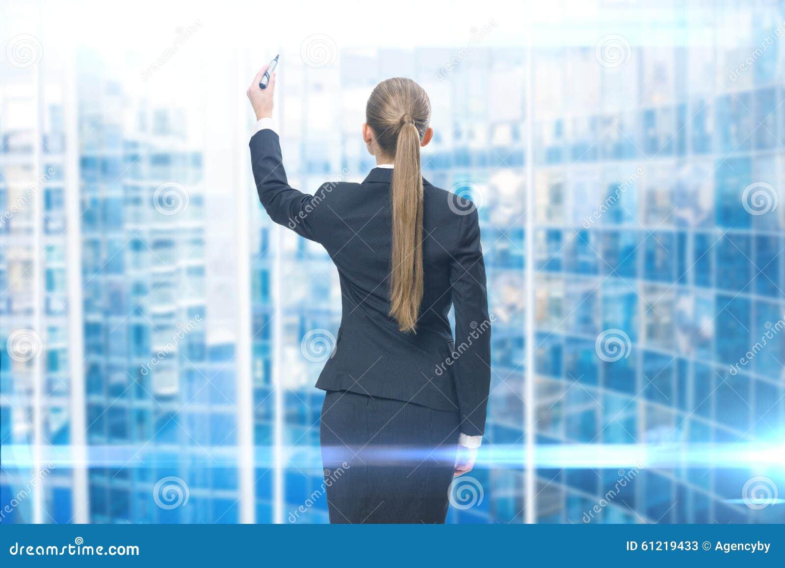 Backview da escrita da mulher de negócios na tela azul