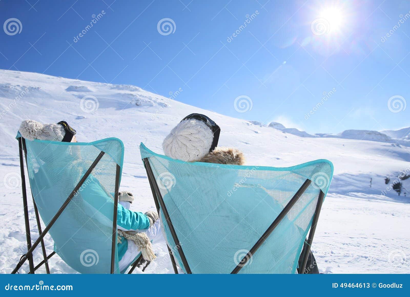Backview de um par que toma o sol no esqui inclina-se