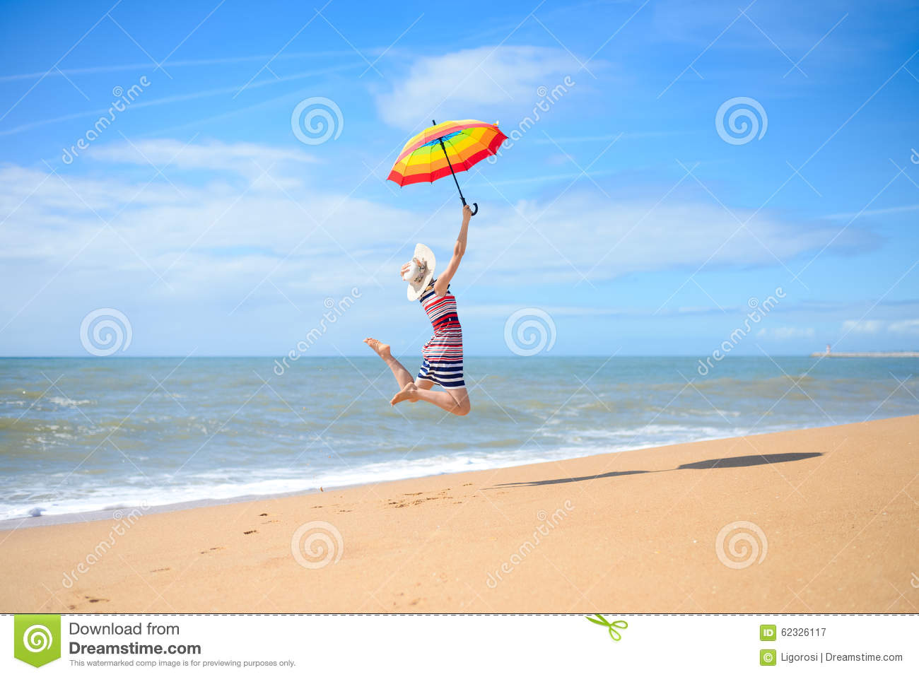 Backview of pretty woman jumping with umbrella on