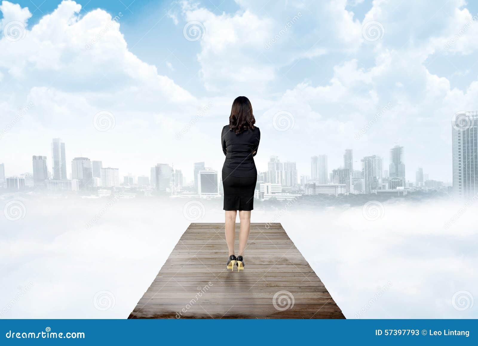 Backview van het bedrijfsvrouw kijken de stad van houten pijler